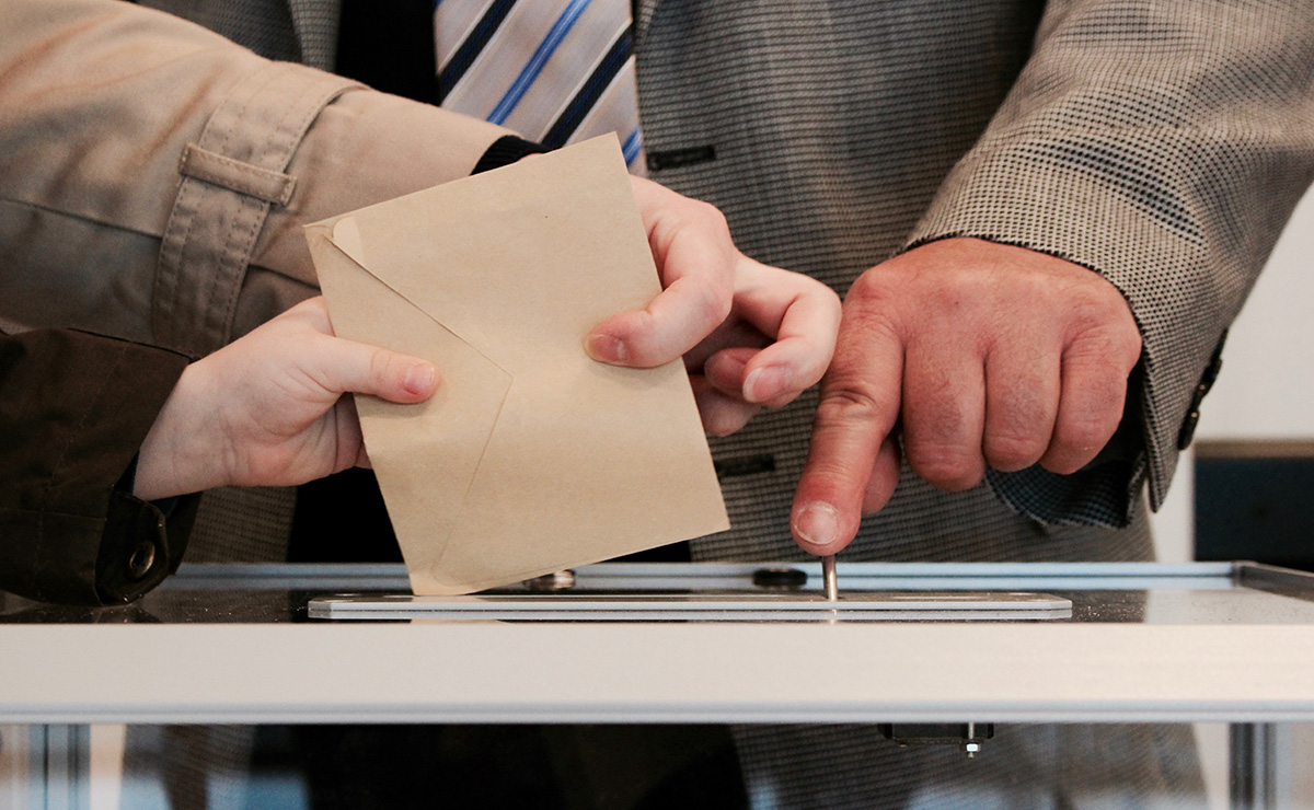 People casting their vote in a polling box