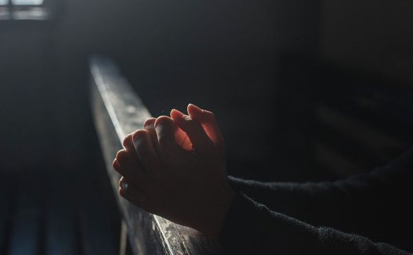 hands clasped in prayer in a dark room