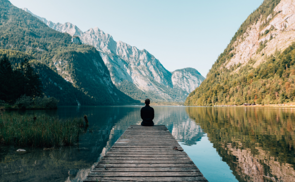 Man sitting on a dock in front of a beautiful vista of a lake and mountains