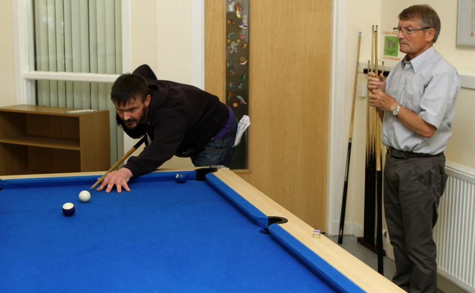 Service user John Ohren having a game of pool at the Havilah Project in Arbroath