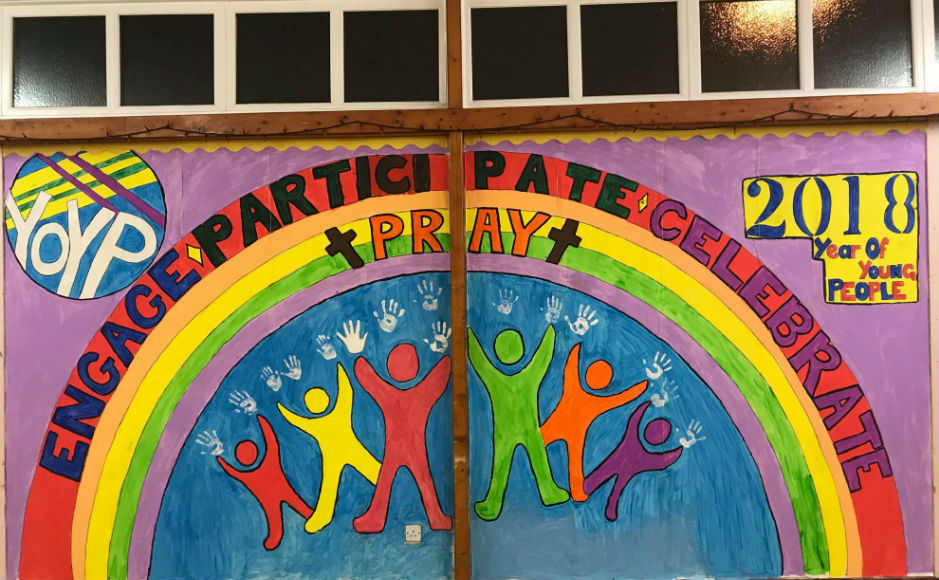 A mural depicting a rainbow, a cross and the year of young people logo