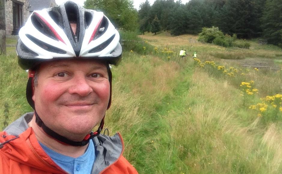 Rev Robert Brookes cycling through a field