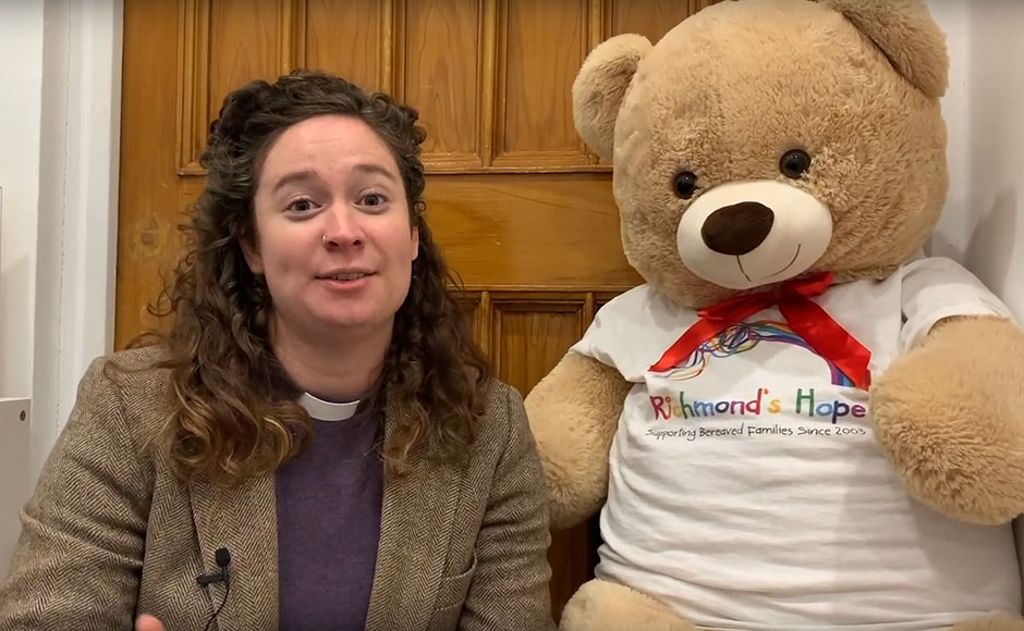 Reverend Tara Granados sitting next to a large teddy bear with Richmond's Hope written on it