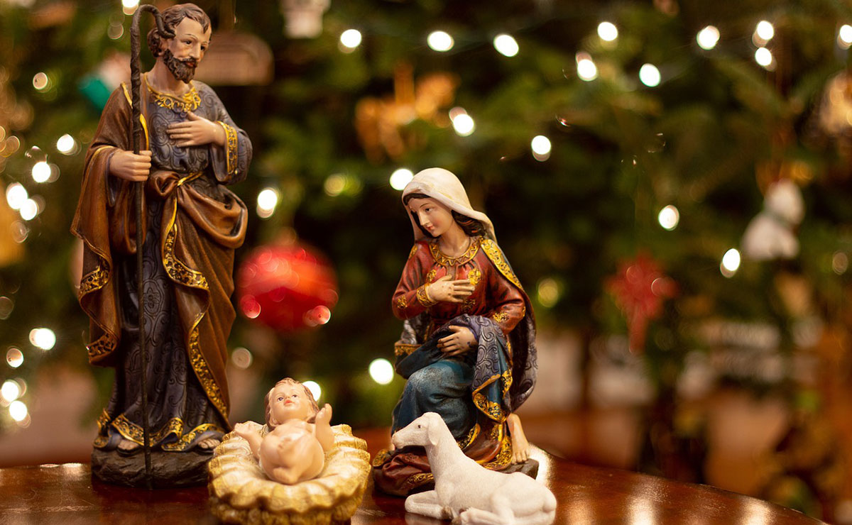 Figures of Mary and Joseph and baby Jesus with Christmas tree in the background