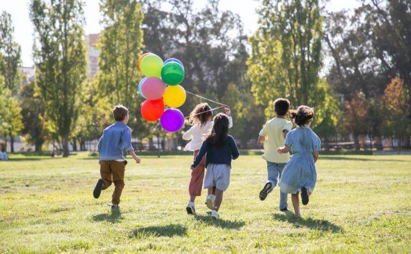 Children running holding balloons