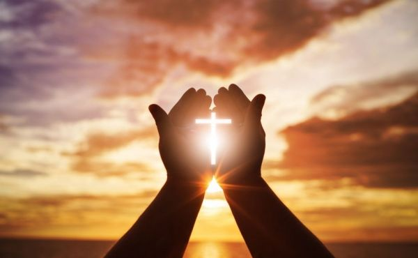 Praying hands with the shape of the cross formed by the sunshine streaming through the hands