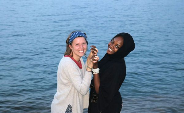Two women holding hands in front of a body of water