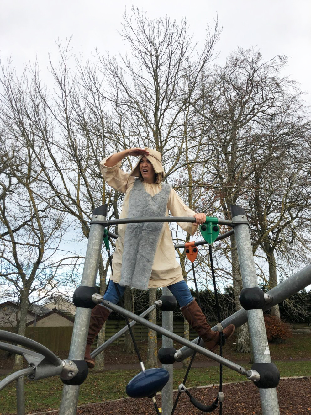 Woman standing in a playground looking around for lost sheep
