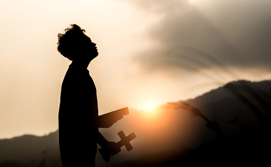Man holding a cross outdoors at sunset