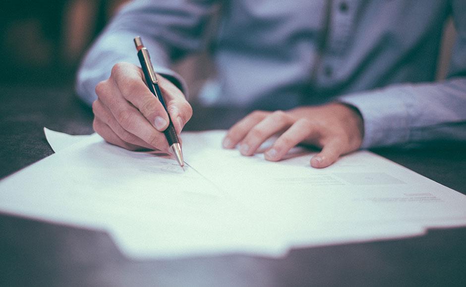 Close up of someone signing paperwork