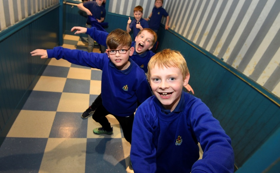 Boys enjoy visual illusions in the Ames room
