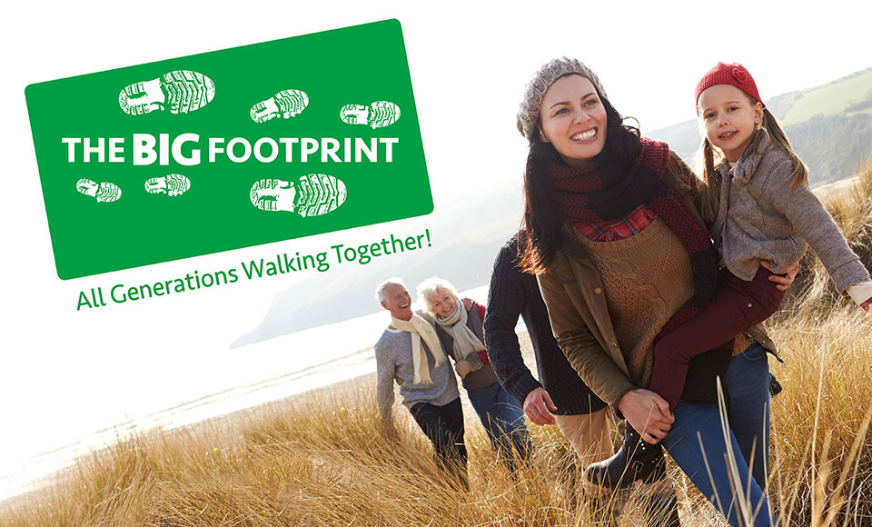 Family out walking with the Big Footprint logo to the left of them