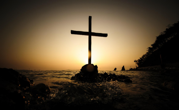 A cross sitting on a rock surrounded by crashing waves at sunset