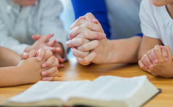 Family's hands praying around a table