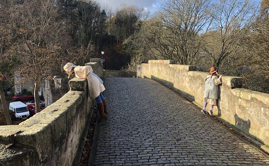 Two people dressed as shepherds looking off a bridge
