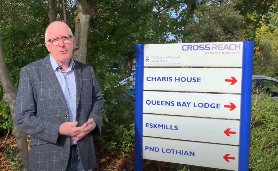 Rt Rev Dr Martin Fair next to a CrossReach sign