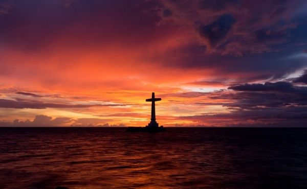 Cross on a rock in the sea at dusk