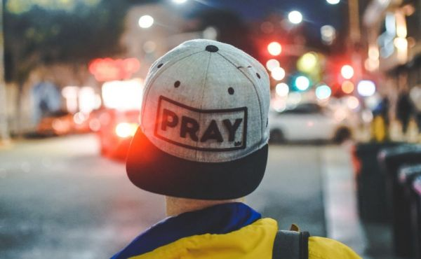 young man wearing cap with pray written on it