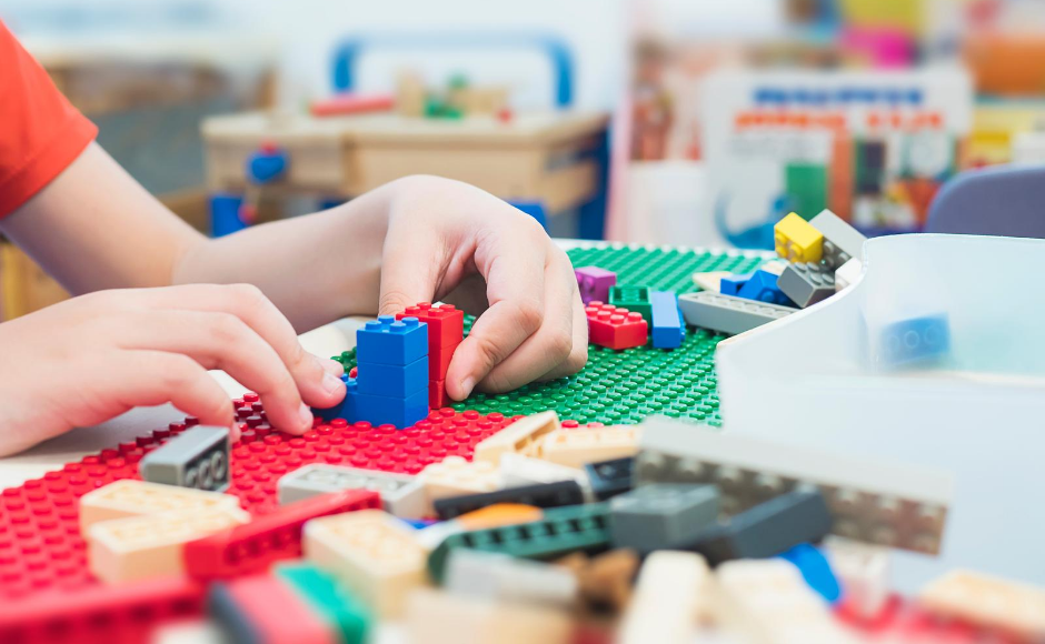 Child's hands playing with lego