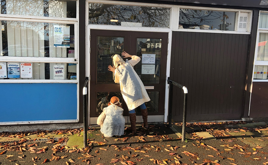 Two people dressed as shepherds look inside a library to see if they can find the lost sheep