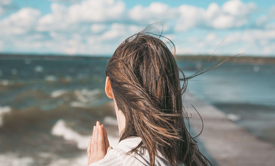 Woman with praying hands looking out to sea