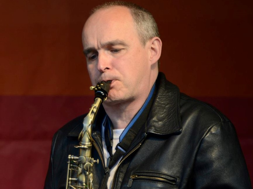 Rev Dr Robin Hill playing a saxophone