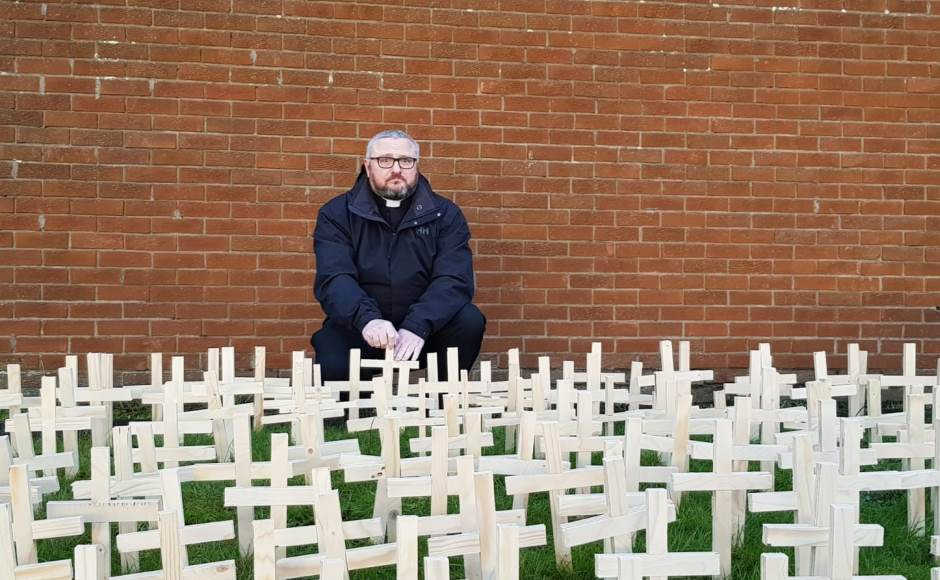 Rev Brian Casey with crosses representing the deaths of drug users