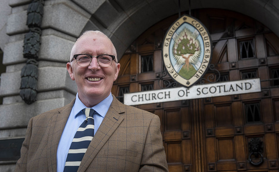 Rev Dr Martin Fair standing in front of the Church of Scotland emblem