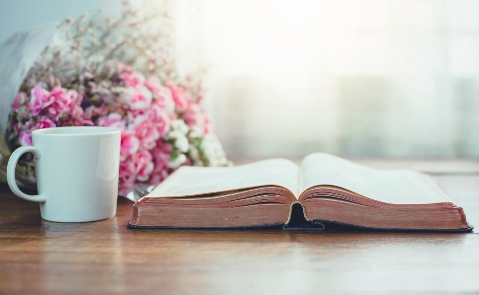 Open Bible on table with a cup of coffee next to it and some pink flowers