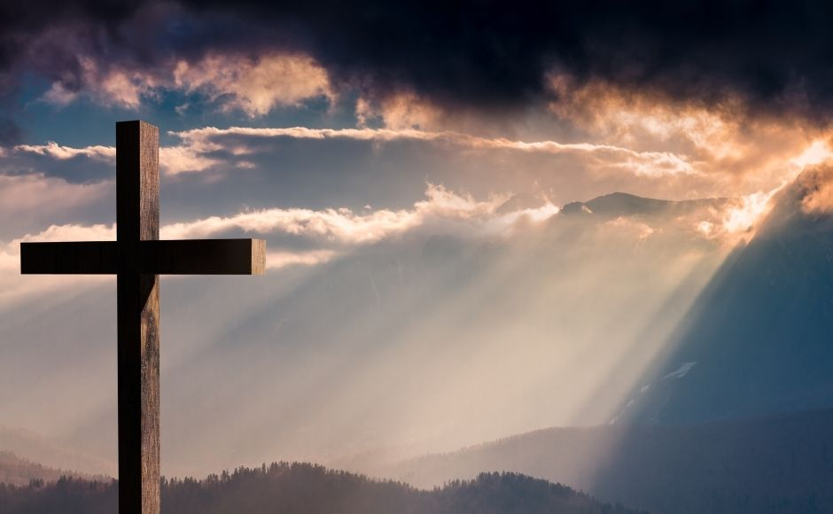 A cross sitting on a hill at sunset